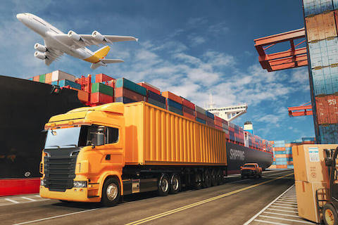 A plane flies over a truck and cargo ship.